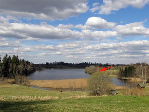 Skats uz Kāpurkalna ezeru no Elka jeb Rata kalna nogāzes. Ar bultiņu norādīts uz aptuveno vietu, kur atrodoties, J.Krams ieraudzīja pils parādību virs ezera.