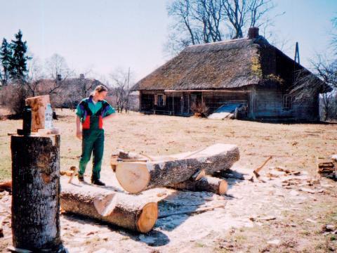"""Edgars Žīgurs """"Virolvēveru"""" pagalmā, darinot vienkoča laivu. Ap 2006. Attēls no E.Žīgura personīgā arhīva."""
