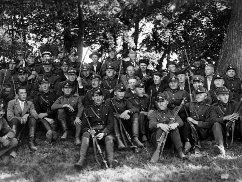 """Valmieras aizsargi pēc šaušanas apmācībām pie """"Daliņiem"""" Valmieras pagastā. Centrā, otrā rindā no augšas (zem smaidošā aizsarga) - Pēteris Kannītis. Pirmajā rindā sēž (roku uz labā ceļa uzlicis) ceturtais no kreisās Arnolds Purgailis. Uz reversa uzraksts: """"uzjemts 19. augustā 1934. g. pie Daliņa mājām pēc I mās rotas skotu šaušanas"""". Attēls no E.Laura personīgā arhīva."""